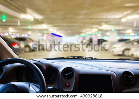 In the car, blur image of parking lot as background.
