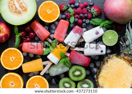 In the center on ice cubes variety of sorbet and ice cream cones near ingredients fruits and berries on black background. Summer coolness of ice cream and sorbet cones. Horizontal. Top view. Close. - stock photo