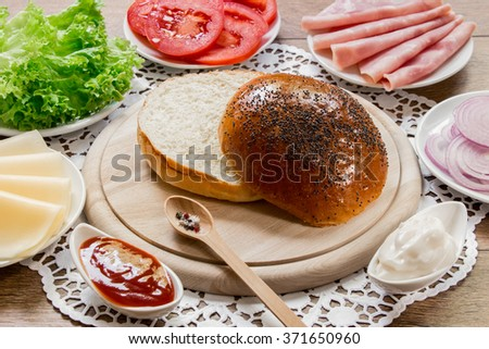 In the center the bun cut in half on a wooden board around ingredients for a sandwich cheese, lettuce, tomato, ham, onion, mayonnaise, ketchup on wooden background. Cooking ham and  cheese sandwich.