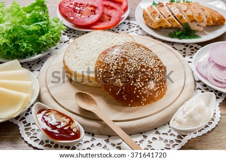 In the center the bun cut in half on a wooden plank around ingredients for a sandwich cheese, lettuce, tomato, chicken, onion, mayonnaise, ketchup on the wooden background. Cooking chicken sandwich. - stock photo