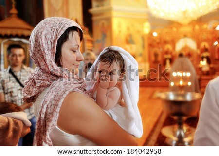 in the church against the icons and lights woman holding a cute baby in her arms - stock photo