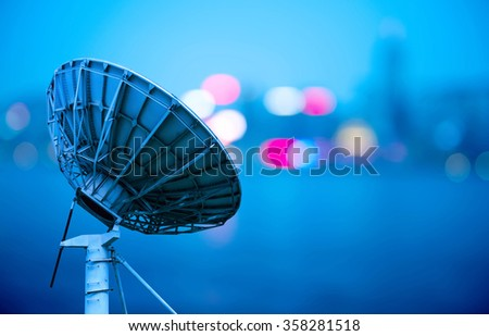 In the city night background large satellite antenna - stock photo