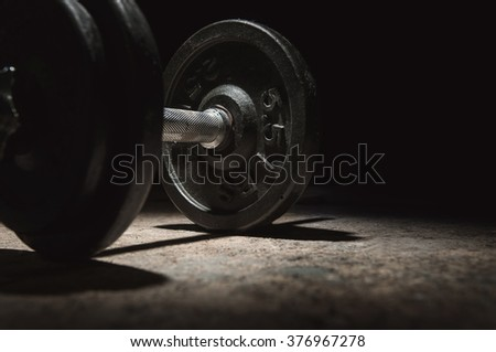 In the dark mood, Close up of dumbbell with lighting and shadow on black background. Copy space. - stock photo