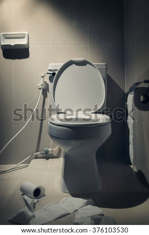 In the dark mood, white toilet with toilet paer in the Bathroom interior. - stock photo