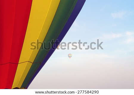 In the distance two hot air balloons can be seen high up in the sky and partially obscured by the fog in the air. In the foreground is a rainbow colored hot air balloon. - stock photo