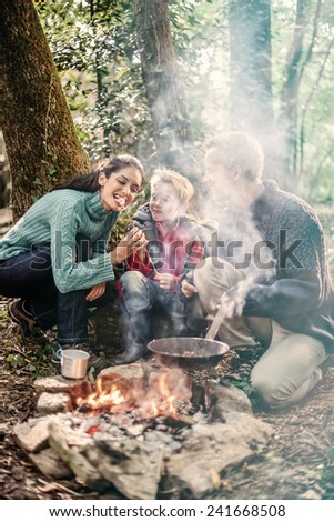 in the evening, cheerful family roasting marshmallows in the woods on a campfire - stock photo