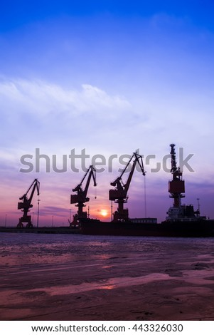 In the evening, the silhouette of port cranes