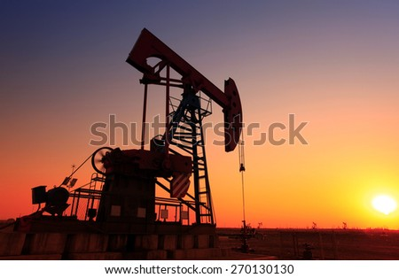 In the evening, the silhouette of the oil pump, it is very beautiful - stock photo