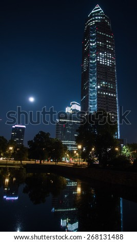 In the exhibition site: Trade Fair Tower, Messeturm, and full moon in Frankfurt, Germany