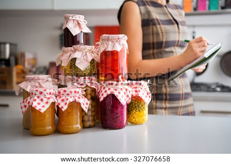 In the foreground, a stack of glass jars filled with home-made preserved vegetables. In the background, the profile of a woman listing the different ingredients before she stores them away for winter. - stock photo