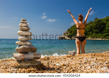 In the foreground is the pyramid of pebbles, the pyramid in focus, in the background there is a girl back to us, the girl raised her hands up/ Pyramid of pebbles and girl/ Love Spa treatments - stock photo