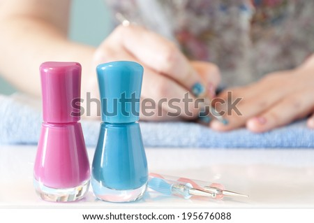 In the foreground there are two nail polishes (one pink and one blue) with manicure tools. In the background out of focus, woman's hands painting her nails