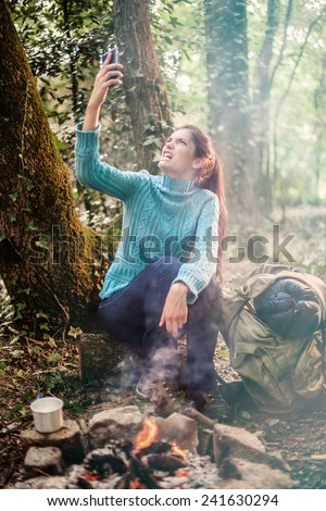 In the forest near a campfire a young angry woman  because a poor reception for her phone - stock photo