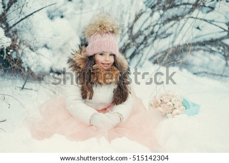 in the forest of snow in winter beautiful girl with long hair in a hat