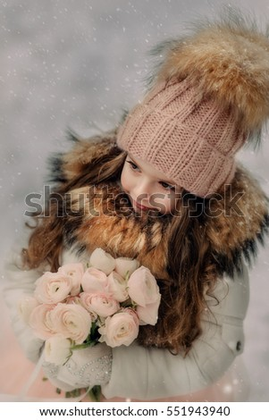 in the forest of snow in winter beautiful girl with long hair in a hat and a bouquet of roses