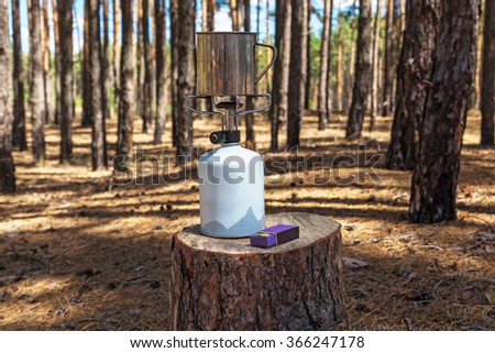 In the forest on the stump items are located a gas burner with a cup of hunting matches - stock photo