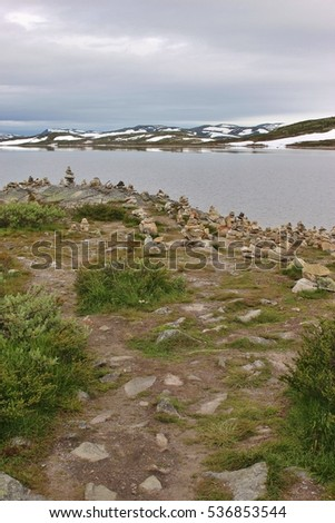 In the Hardangervidda national park, or Hardanger mountains plateau, in Norway, Europe. In August, there is still snow on the mountains. Height above sea level approx. 1100 meters.
