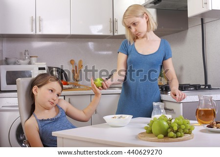 in the kitchen. a child refuses to eat, mom makes daughter eat healthy. mom and daughter eating Breakfast, the child is not eating. quarrels, conflicts in the family. offers baby apple