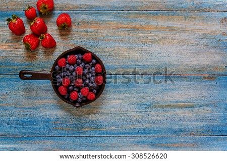 In the kitchen, bakery, cook pan left on the table with berries, side by side on a wooden table lie the few remaining strawberries - stock photo