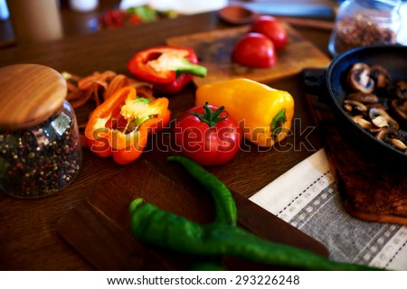 In the kitchen, vegetarian restaurant chef chopped pepper and tomatoes mushrooms are already close to the pan fried - stock photo