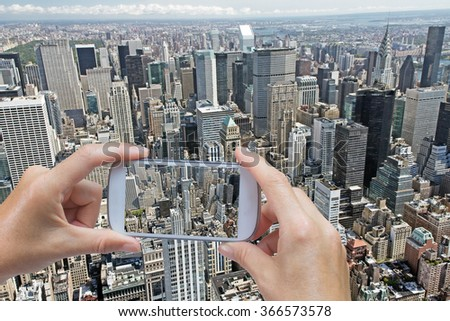 In the left bottom of the photo are hands holding smart phone and taking aerial picture of Manhattan wth Fifth Avenue in New York City (USA). All potential trademarks are removed. - stock photo