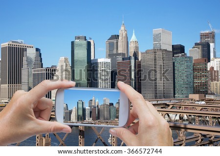 In the left bottom of the photo are hands holding smart phone and taking picture of Lower Manhattan skyscrapers from Brooklyn Bridge (New York City, USA) - stock photo