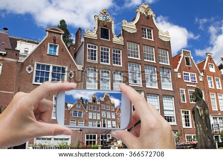 In the left bottom of the photo are hands holding smart phone and taking picture of traditional architecture in Amsterdam (Netherlands) - stock photo