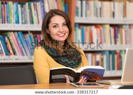 In The Library - Beautiful Female Student With Laptop And Books Working In A High School - University Library - Shallow Depth Of Field