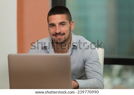 In The Library - Handsome Male Student With Laptop And Books Working In A High School - University Library - Shallow Depth Of Field - stock photo