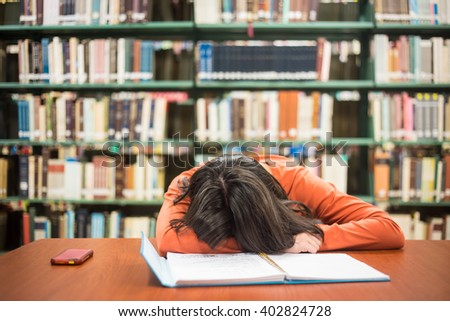 In the library - lazy bored pretty female student with books working in a high school library. - stock photo