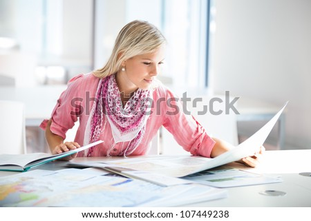 in the library - pretty female student with books working in a high school library (color toned image) - stock photo