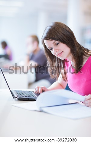 in the library - pretty female student with laptop and books working in a high school library  (color toned image)