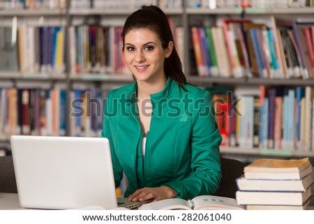 In The Library - Pretty Female Student With Laptop And Books Working In A High School Or University Library - Shallow Depth Of Field