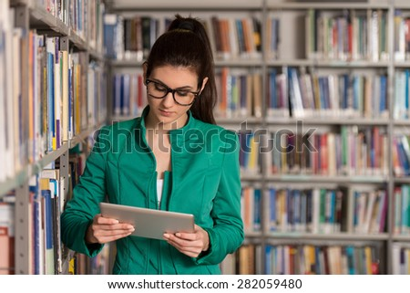In The Library - Pretty Female Student With Tablet And Books Working In A High School - University Library - Shallow Depth Of Field - stock photo