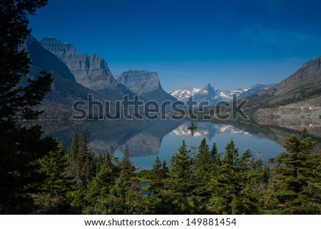 In the middle of St. Mary Lake in Glacier National Park is a small island halfway between two shores called wild goose island. - stock photo