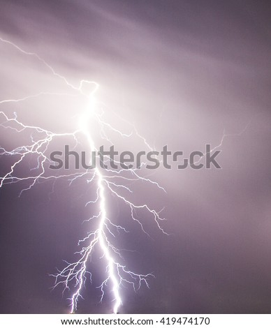 In the middle of the storm a bolt of lighting comes out of the sky - stock photo