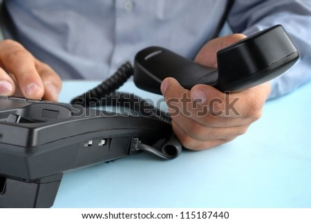 in the office of a man holding up the phone - stock photo