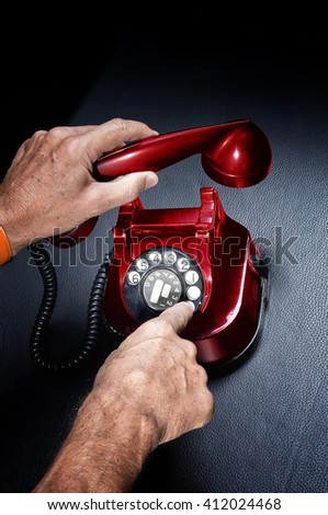 In the office of a man holding up the vintage red phone - stock photo