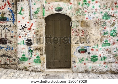 In the Old City of Jerusalem, many doorways of Arab families show where they have made religious pilgrimages to Islamic sites through paintings on the walls near the door. - stock photo