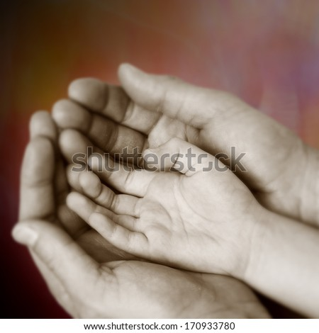 In the palm of the hands of an adult's hand therein in an attitude of a child protection - stock photo