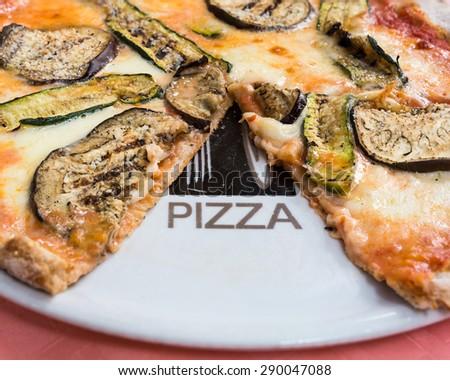 In the picture a whole wheat pizza with eggplant , zucchini , tomato and Neapolitan buffalo mozzarella.( Bufala campana) - stock photo