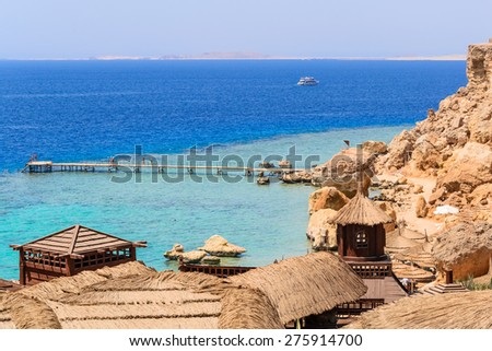 in the picture bungalow in wood and straw are located on the rock coast of the Red Sea in Egypt. - stock photo