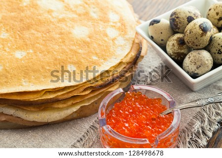 In the pile pancakes with caviar and quail eggs - stock photo