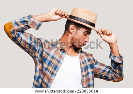 In the rhythm of my life. Handsome young Afro-American hipster holding hands on his hat while standing against grey background - stock photo