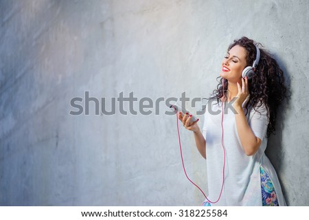 In the rhythm of my music. Happy young brunette woman in headphones with smartphone leaning on  wall and listening to the music. - stock photo