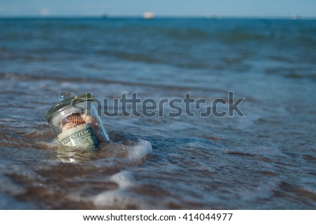 in the sand in the surf is the glass jar with money and shells, gift sea