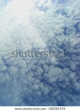 In the sky above the clouds with the sun behind the clouds - stock photo