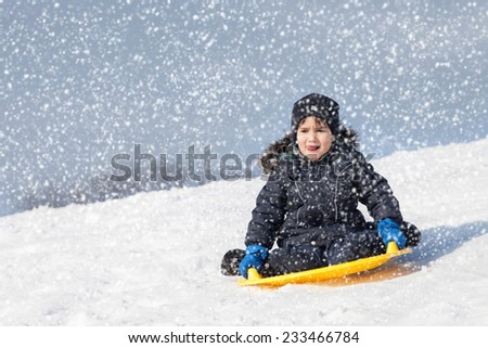 In the snowfall. Boy on sleigh. Sledding at winter time - stock photo