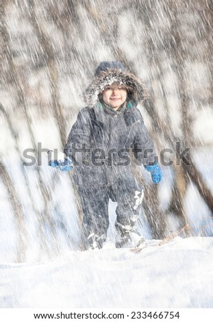In the snowfall. Cute boy walk in the winter park - stock photo
