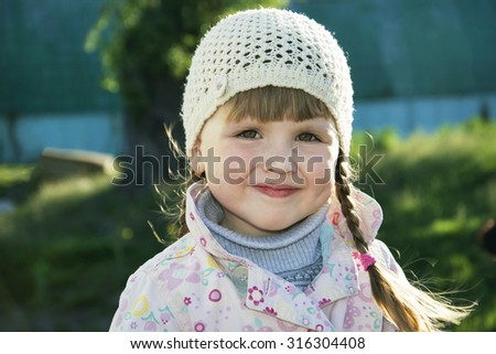 In the spring on the street beautiful little girl. Close-up. - stock photo